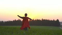 Young boy with a Superman cape outdoors in a field during sunset - stock footage