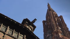 Strasbourg cathedral tower with roof of medieval house in front Stock Footage