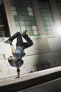 A young man breakdancing on the street of a city, doing a one handed handstand. - stock photo