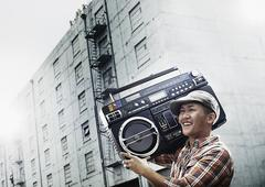 A young person with a boombox on the street of a city. Kuvituskuvat