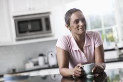 A woman leaning on the smooth countertop of her kitchen unit - stock photo