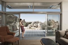 A woman and a young child in the living space of an eco house in the desert. Stock Photos