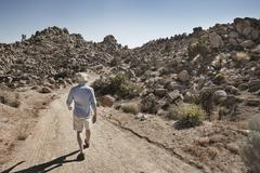 A man walking along a path in a rocky landscape, dry and arid. - stock photo