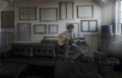 Wall hung with picture frames. A man playing a guitar. Stock Photos