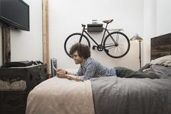 Loft living. A bicycle hanging on a wall. A man using a digital tablet. Stock Photos