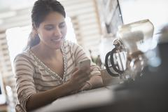 Loft living. A woman looking at her smart phone. Stock Photos