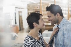 A woman adjusting a man's tie, smiling at him. Stock Photos