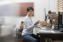 A woman in a home office with a desk with two laptops, checking her smart phone. Stock Photos