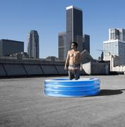 A man standing in a small inflatable water pool on a city rooftop. Kuvituskuvat