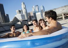 A group of friends sitting in a small inflatable water pool on rooftop Stock Photos