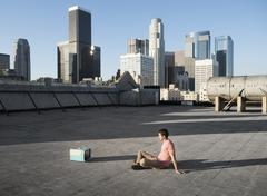 A man sitting on a city rooftop watching a small blue portable television. - stock photo