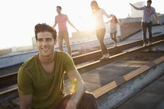 A group of people on a rooftop at dusk walking along steel struts on the roof. Stock Photos