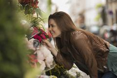 A woman bending to smell the scent of flowers at a stall on the street. - stock photo