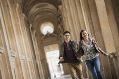 A young couple walking down a colonnade in the historic heart of a city. - stock photo
