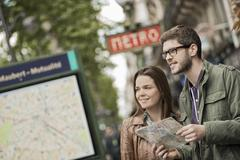 A couple using a street map beside an information sign under a metro sign - stock photo