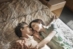A young couple lying side by side on top of the bed in a motel room. - stock photo