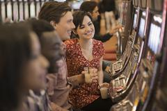 A group of people playing the slot machines in a casino. - stock photo
