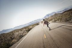A young man riding down a tarmac road in the desert on a skateboard. Stock Photos
