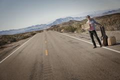 Hitchhiker with guitar and case, holding a sign saying Vegas or Bust. Stock Photos
