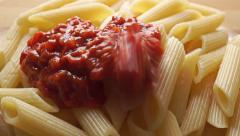 Adding dense red vegetable sauce to freshly cooked pasta (penne) - stock footage