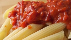 Freshly cooked pasta (penne) covered with red vegetable sauce, dolly shot - stock footage