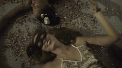 Young adult women on floor at party with confetti Stock Footage