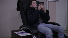 Teen sitting in a massage chair with smartphone Stock Footage
