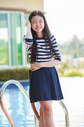 portrait of asian teen age smiling face standing in home swiming pool with re - stock photo