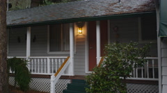Zoom-in on motel cabin door beside a glowing porch light - stock footage