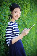 portrait of asian teen age ,girl with computer tablet in hand standing agains - stock photo