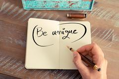 Handwritten text BE UNIQUE - stock photo