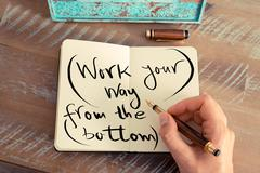Handwritten text WORK YOUR WAY FROM THE BOTTOM Stock Photos