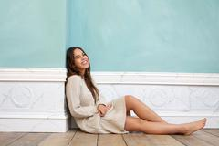 Young woman smiling and sitting on wood floor at home - stock photo