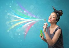 Beautiful girl blowing abstract colorful bubbles and lines Stock Photos