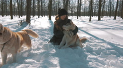 Happy young woman hugging and patting siberian husky dog in snow forest, 4k - stock footage