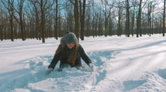 Pretty young woman throwing snow up in the air and having fun in snow forest, 4k Stock Footage