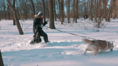 Young woman running with siberian husky dog in snow forest, slow motion - stock footage