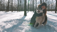 Young woman having fun with siberian husky dog in snow forest, 4k - stock footage