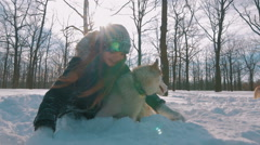 Young woman throwing snow up and patting husky dog in snow forest,slow motion - stock footage