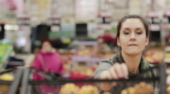 Young woman chooses ripe oranges on store shelves Stock Footage