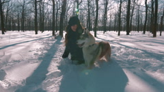 Young girl sitting and throwing snow at siberian husk in snow forest,slow motion - stock footage