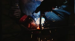 A man working in a factory with welding Stock Footage