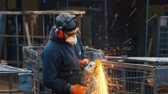 A man in overalls working on welding Stock Footage