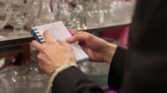 Closeup of a man with a shopping list in a notebook - stock footage