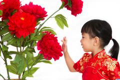 Chinese little girl wearing in Red posing with flowers Stock Photos