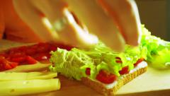 Placing leaf of fresh green salad on a sandwich Stock Footage