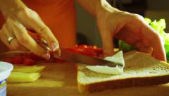 Girl hand spreading soft cheese on a slice of bread - stock footage