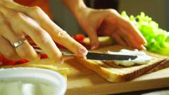 Making a sandwich: spreading soft cheese on a toasted bread - stock footage