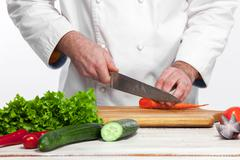 Chef cooking fresh vegetable salad in his kitchen - stock photo
