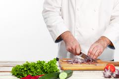 Chef cutting a onion on his kitchen - stock photo
